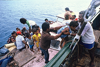 Rainbow Warrior crew helping Rongelap islanders board the ship for one of four voyages relocating them to Mejato islet in May 1985. Image: David Robie/Eyes of Fire