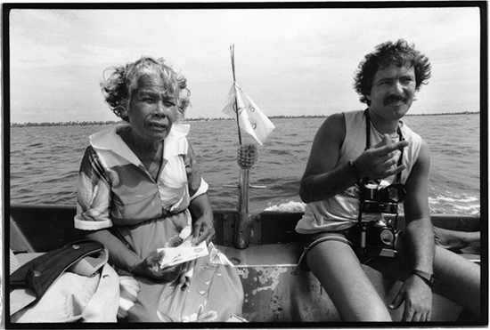 "ernando Pereira and Rongelap Islander Bonemej Namwe ride ashore in the ""bum bum"" runabout at Rongelap in May 1985. Born on Kwajalein, Namwe, was then aged 62 and had lived most of her life on Rongelap. Image: David Robie/Eyes of Fire"