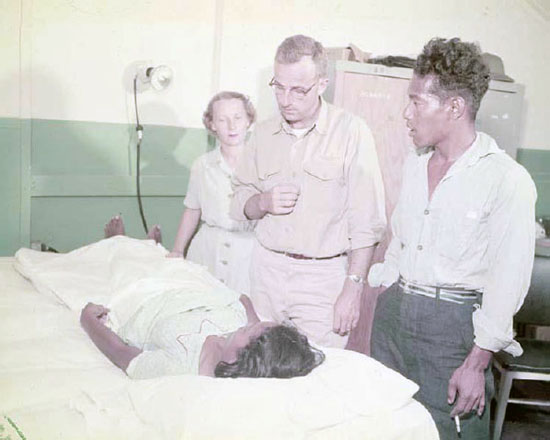 Jabwe, the Rongelap health practitioner, assists Nurse Lt. M. Smith and Dr. Lt. J. S. Thompson, during a medical examination on Kwajalein, 11 March 1954. From DTRIAC SR-12-001.
