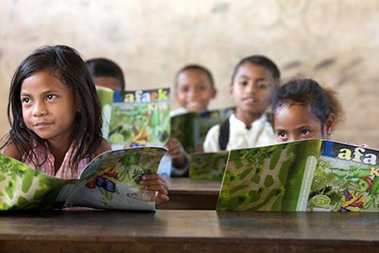 School children at Leo Hitu Primary School read their copies of CARE educational magazine, Lafaek in Bobonaro, Timor-Leste. Image: Jane Dempster/CARE