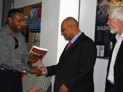 Henry Yamo, one of the book authors, presents a signed copy to PNG High Commissioner William Dihm. Photo: Del Abcede