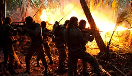 A flame thrower clears the jungle before the cave in the final assault at Gossanna. Image: Rebellion